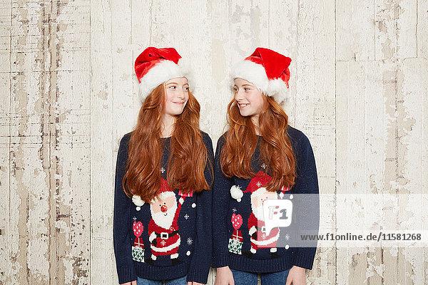Porträt von Zwillingsschwestern mit Weihnachtspullovern und Hüten