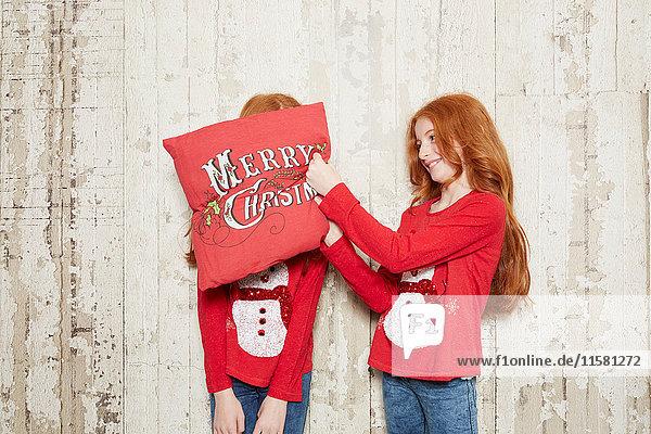 Porträt von Zwillingsschwestern in Weihnachtspullovern  eine Schwester bedeckt das Gesicht der Schwester mit einem Kissen