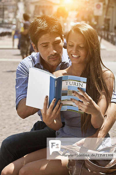 Young couple looking at guidebook  Turin  Piedmont  Italy
