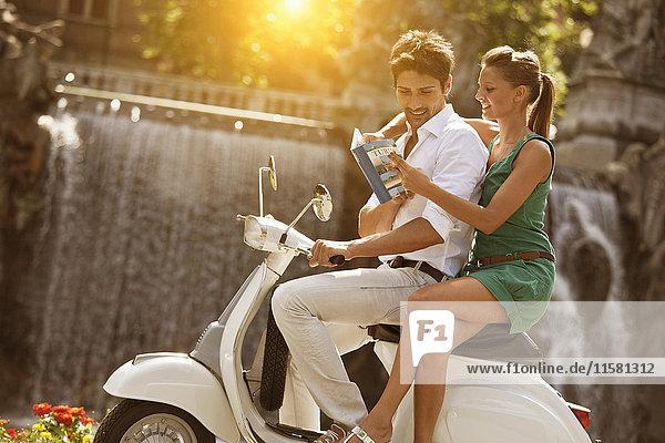 Junges Paar sitzt auf einem Roller und schaut sich einen Reiseführer an  Turin  Piemont  Italien