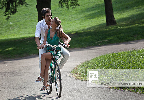 Young couple riding bicycle through park  Turin  Piedmont  Italy