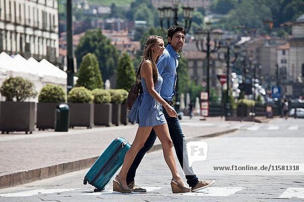 Young couple crossing road  pulling suitcase  Turin  Piedmont  Italy