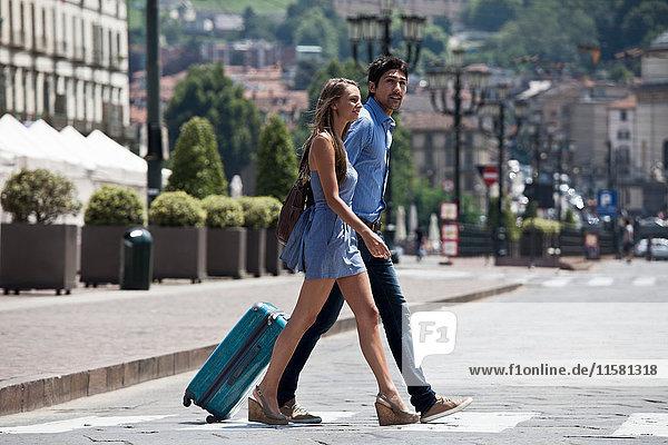 Junges Paar überquert Straße  zieht Koffer  Turin  Piemont  Italien