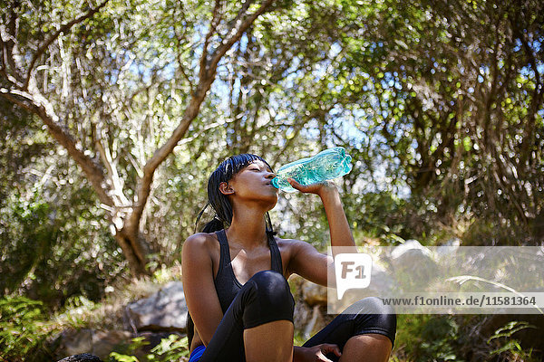 Young woman sitting outdoors  wearing sports clothing  drinking from water bottle