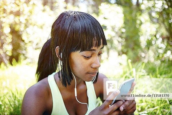 Young woman in rural setting  using smartphone  wearing earphones