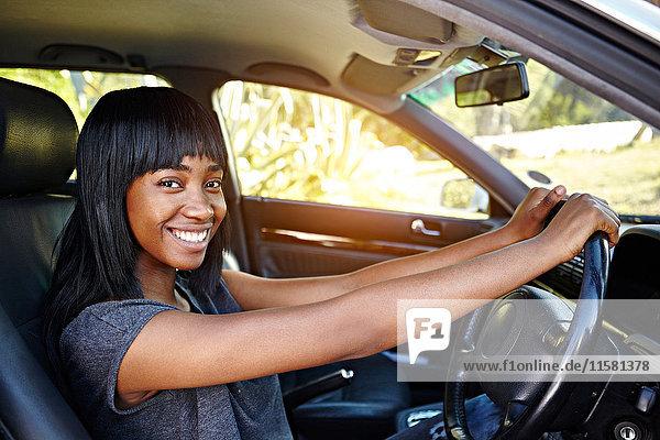 Porträt einer jungen Frau beim Autofahren