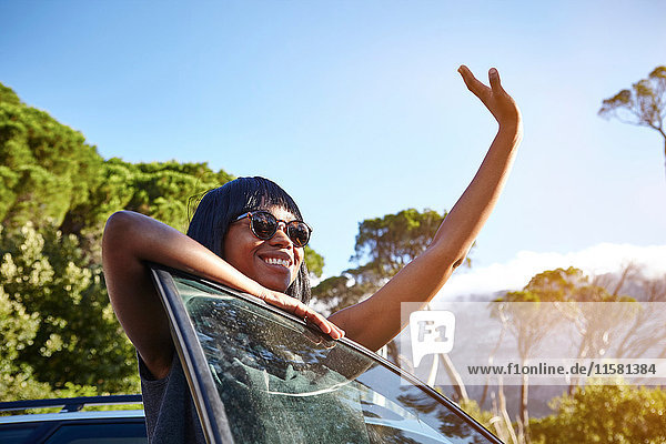 Portrait of young woman standing beside car  leaning on open car door  waving