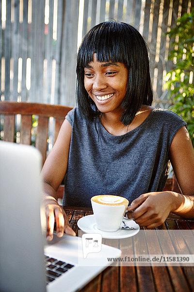 Junge Frau sitzt im Freien  benutzt Laptop  trinkt Kaffee