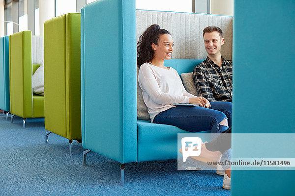 Universitätsstudenten entspannen sich in einem modernen Kabinen-Sitzbereich