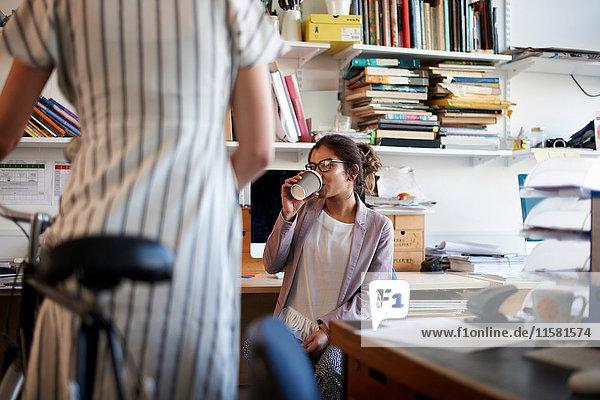 Frau im Büro trinkt Kaffee und unterhält sich mit ihrem Kollegen