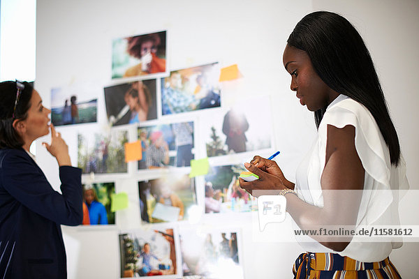 Colleagues in office discussing photographs on wall