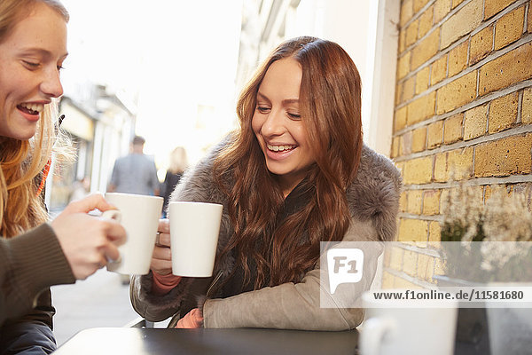 Two female friends  sitting outdoors  drinking coffee  laughing