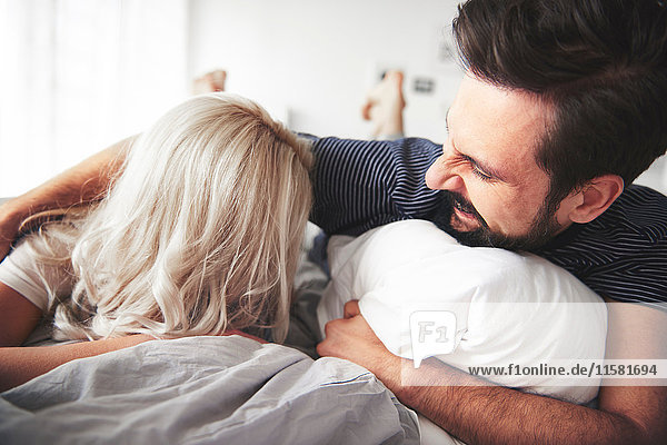Auf dem Bett liegendes Paar  Mann kitzelt Frau