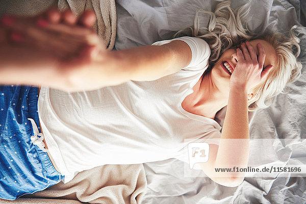 Frau liegt auf Bett  Mann zieht sie vom Bett  erhöhte Ansicht