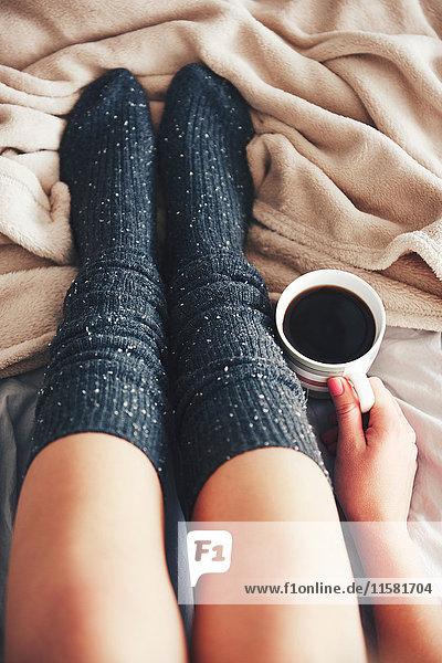 Frau sitzt auf dem Bett  trägt warme Socken  hält eine Tasse Kaffee  niedriger Schnitt  Draufsicht