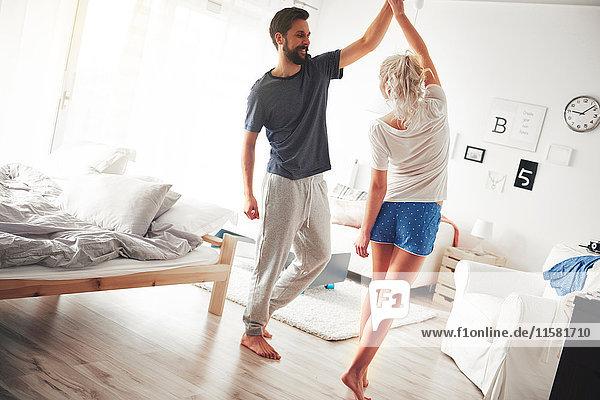 Paar im Schlafzimmer  im Pyjama  tanzend