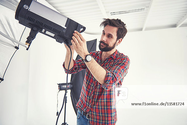 Male photographer preparing photo shoot lighting equipment in studio