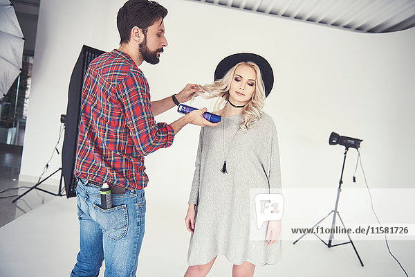Male photographer adjusting female model's hair on studio white background