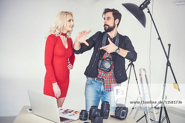 Male photographer explaining to female model for studio photo shoot