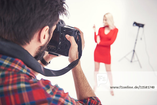Over shoulder view of male photographer photographing female model on studio white background