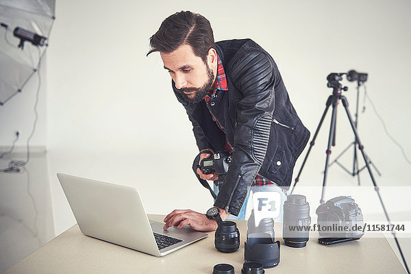 Male photographer reviewing studio photo shoot on laptop