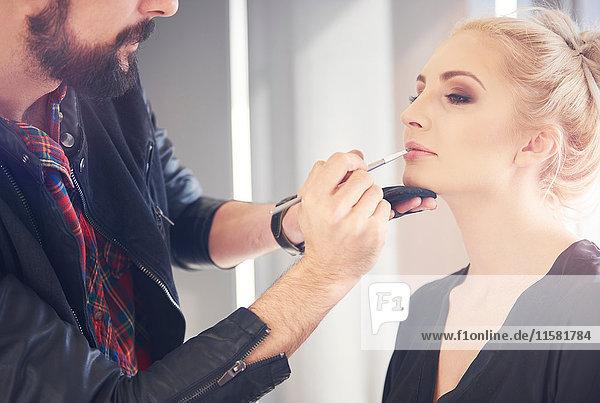 Männlicher Make-up-Künstler trägt Lippenstift auf Modell für Fotoshooting auf