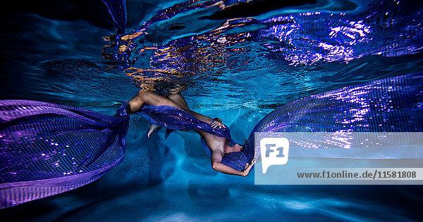 Unterwasseransicht einer balancierten Frau  die in fließende violette Textilien gehüllt ist