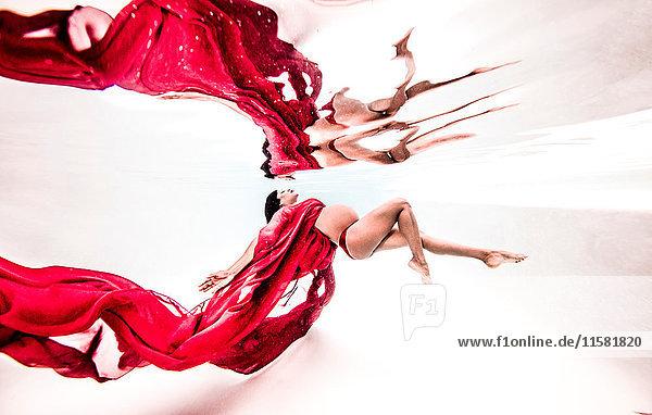 Unterwasseransicht einer balancierten jungen schwangeren Frau mit fließendem roten Stoff