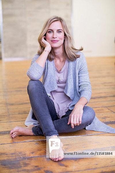 Porträt einer mittelgroßen erwachsenen Frau  auf dem Boden sitzend  den Ellbogen auf dem Knie ruhend  lächelnd