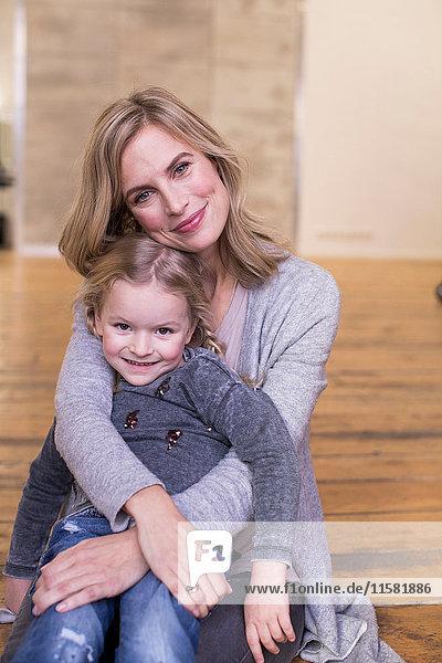 Porträt von Mutter und Tochter  auf dem Boden sitzend  lächelnd