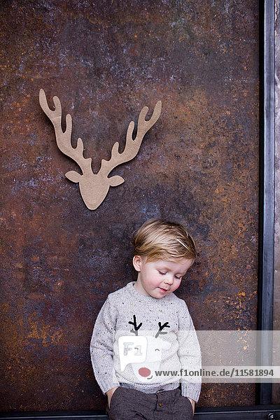 Porträt eines kleinen Jungen  Papprentier an der Wand hinter ihm ausgeschnitten