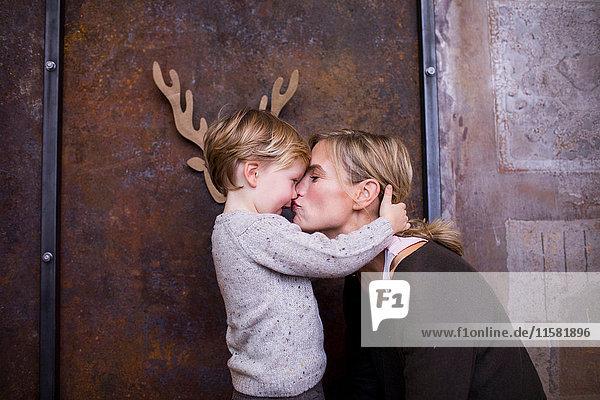 Junger Junge umarmt Mutter  lächelt