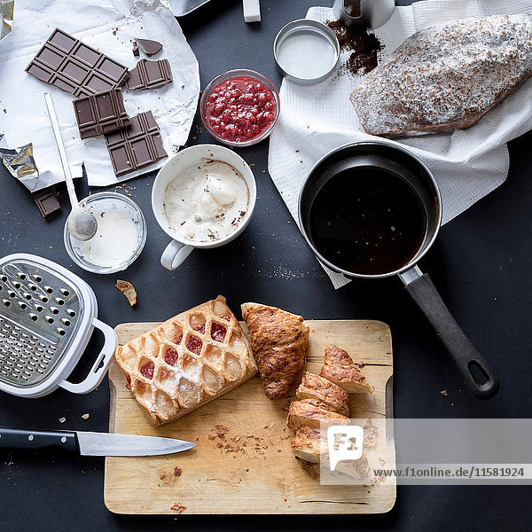 Overhead view of apple strudel  chocolate  cake and ingredients on kitchen table