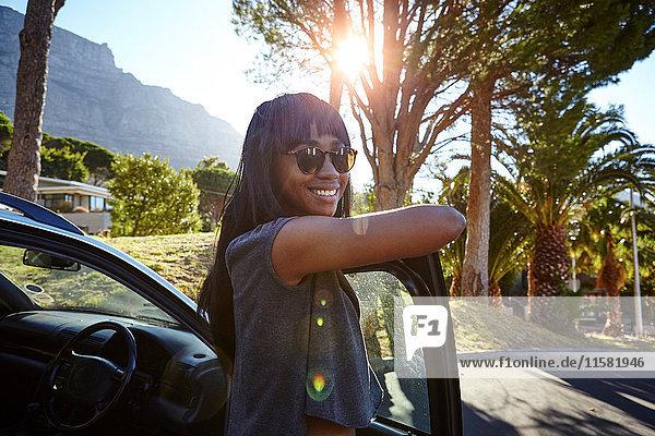 Porträt einer jungen Frau  die neben dem Auto steht und sich an eine offene Autotür lehnt