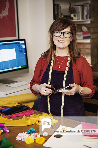 A woman with a measuring tape around her neck  holding a template and brightly coloured fabric and craft materials on the table.