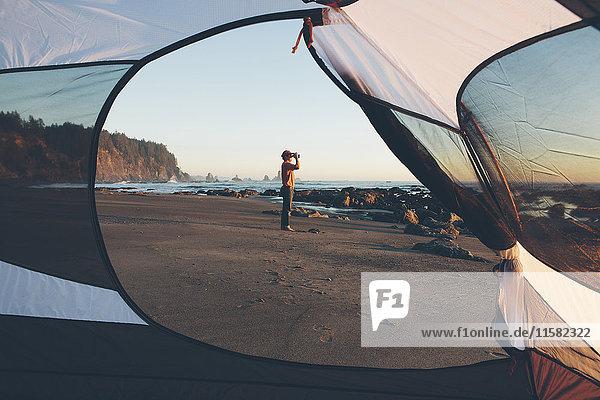 Mann  eingerahmt von einem Campingzelt  steht am Strand und schaut in der Dämmerung durch ein Fernglas  Olympic National Park  Washington  USA.