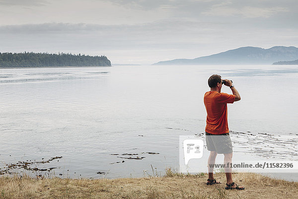 Man standing on a beach  looking through binoculars  San Juan Islands in the distance  Washington  USA.