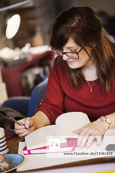 Eine Frau sitzt an einem Tisch  macht Notizen und schreibt in ein Notizbuch.