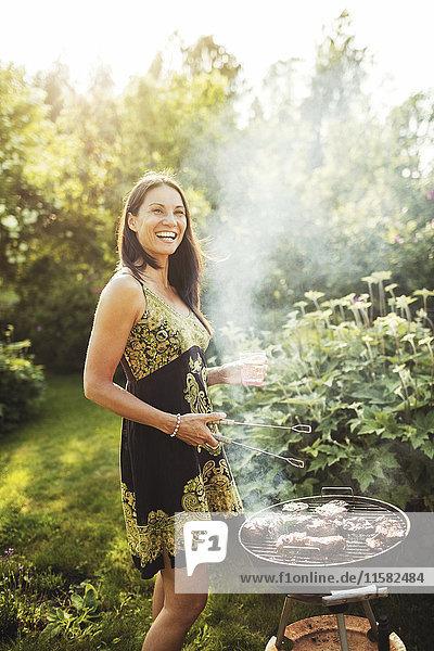 Fröhliche Frau beim Grillen im Hinterhof