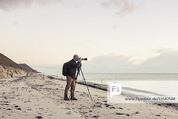 Durchgehende Seitenansicht des Wanderers durch die Spiegelreflexkamera am Strand