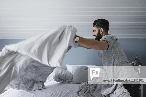 Seitenansicht des Mannes  der das Bett zu Hause macht