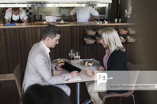 Geschäftsmann zeigt der Kollegin ein digitales Tablett  während sie im Restaurant am Tisch sitzt.