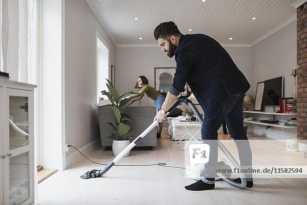 Mann saugt Boden  während Frau im Wohnzimmer zu Hause arbeitet