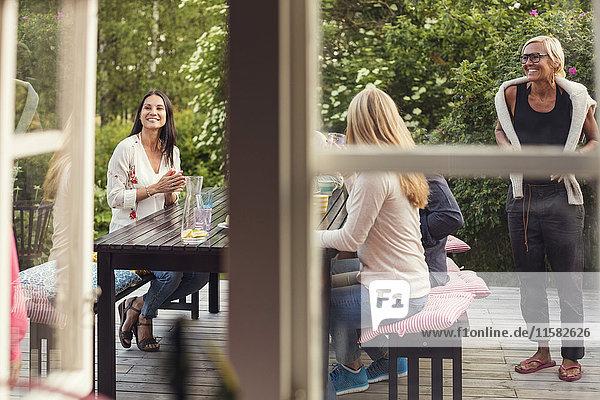 Frauen und Teenagermädchen am Esstisch vom Fenster aus gesehen