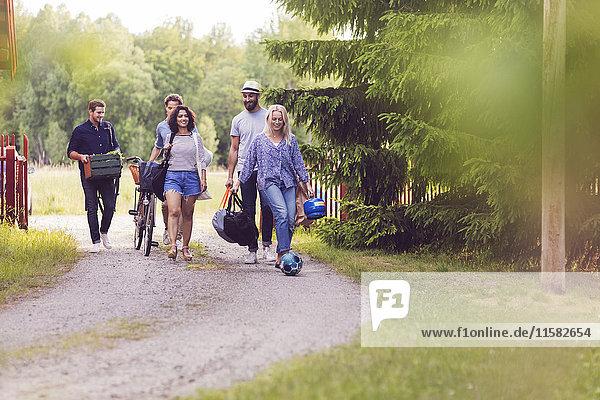 Volle Länge der Freunde mit Gepäck und Radwandern auf dem Fußweg