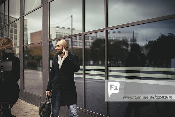 Lächelnder Geschäftsmann im Gespräch mit dem Handy beim Spaziergang durch das Stadtgebäude