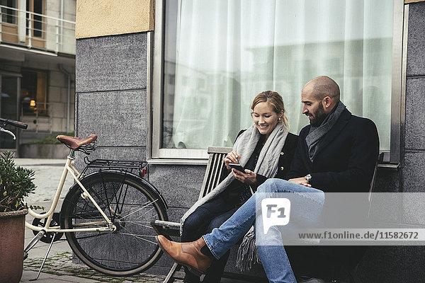 Mittlere erwachsene Geschäftsleute  die das Smartphone auf der Bank gegen das Gebäude benutzen.