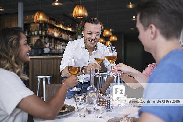 Glückliche Kollegen stoßen beim Geschäftsessen im Restaurant an.