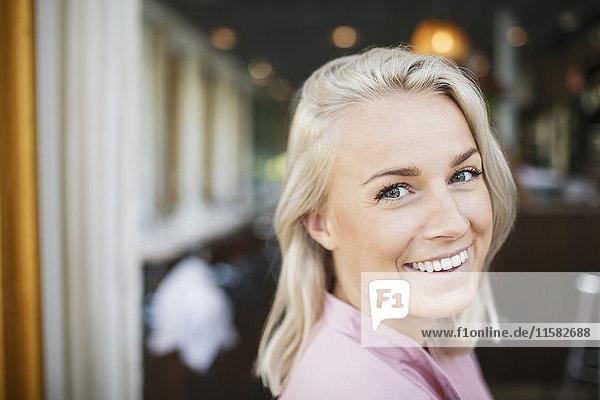 Portrait of happy blond businesswoman at restaurant