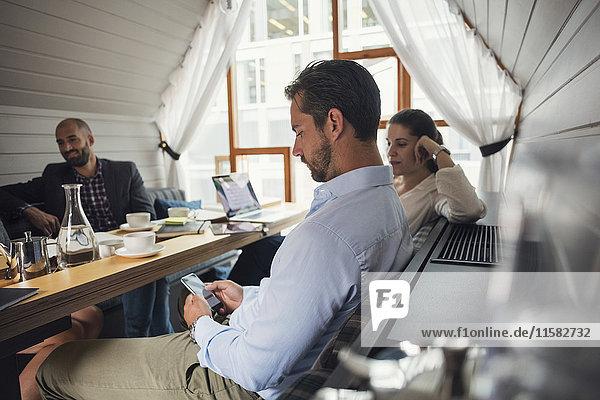 Mittlerer erwachsener Geschäftsmann mit Handy am Tisch während der Bürobesprechung